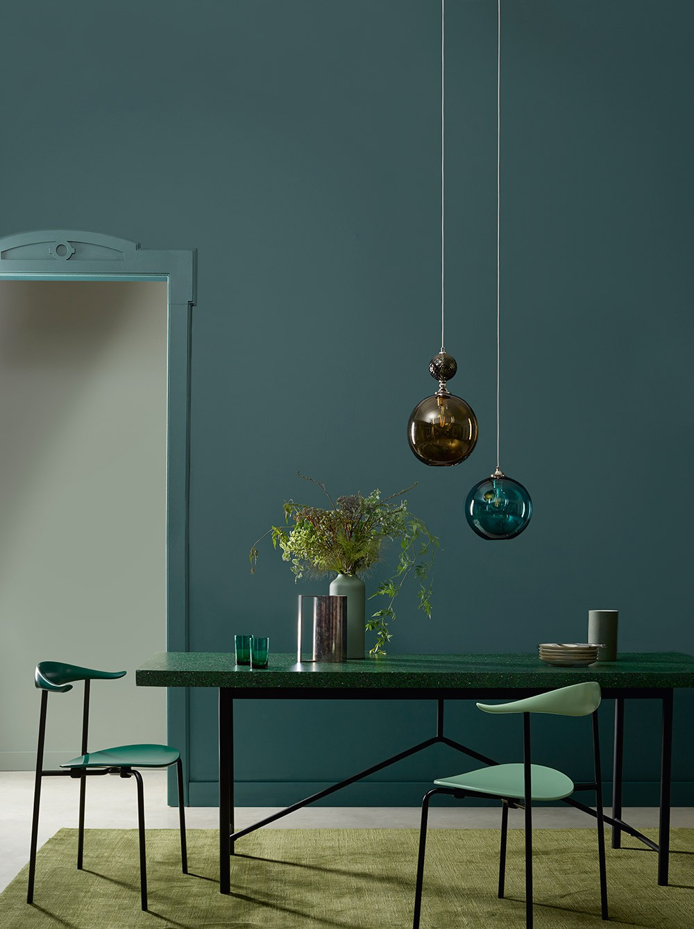 Green dining table with pendant lighting